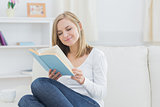 Happy woman reading storybook at home