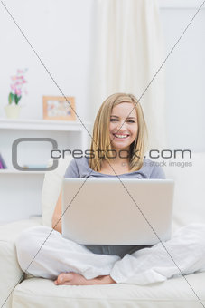 Portrait of relaxed happy woman using laptop on sofa