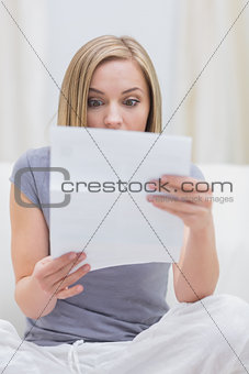 Casual woman reading letter in living room