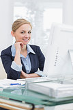 Smiling confident business woman at office desk