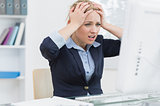 Frustrated business woman in front of computer at office desk