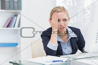Displeased business woman at office desk