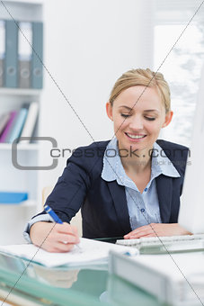 Business woman writing notes at office desk