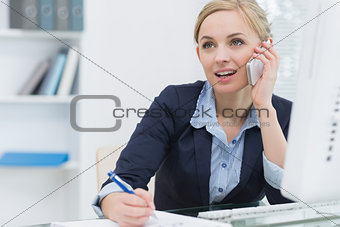 Business woman writing while on call at office