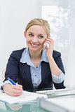 Smiling business woman writing while on call at office