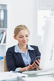 Young business woman text messaging at office desk