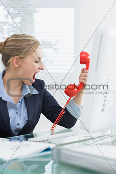 Female executive yelling into red telephone receiver at desk