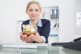 Portrait of business woman with golden piggy bank at office