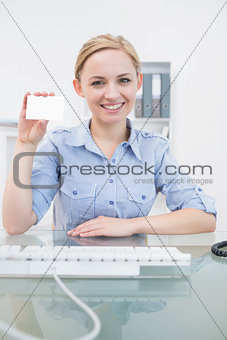 Portrait of female executive holding blank card at office