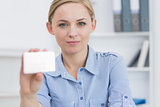 Female executive holding blank card at office
