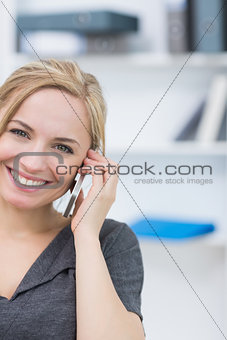 Smiling business woman using mobile phone in office