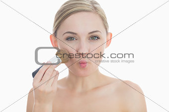 Portrait of young woman putting on makeup