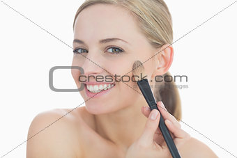 Portrait of smiling young woman putting on makeup