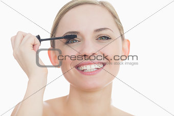 Portrait of young woman applying mascara to her eye