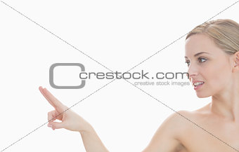 Beautiful young woman pointing at invisible screen