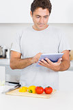 Man consulting tablet while chopping vegetables