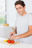 Smiling man slicing peppers