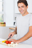 Smiling man preparing vegetables