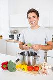 Man putting broccoli in pot