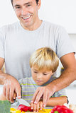 Father helping son to slice vegetables