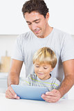 Son and father using tablet together
