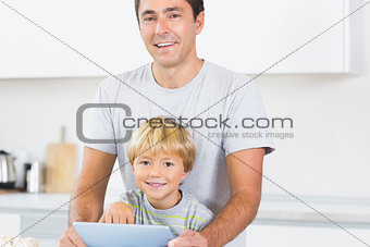 Happy father and son using tablet computer
