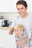 Happy father and son using laptop