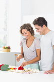 Smiling couple preparing vegetables