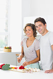 Smiling wife chopping vegetables with husband