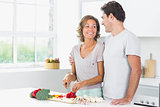 Husband embracing wife as she prepares vegetables