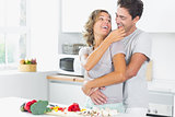 Wife jokingly feeding husband in kitchen