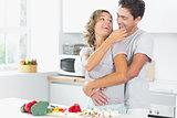 Wife jokingly feeding husband in kitchen