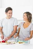 Smiling couple making salad together