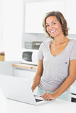 Woman standing in kitchen with laptop