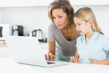 Mother and daughter using laptop