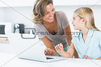 Smiling mother and daughter with laptop