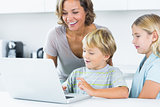 Mother using laptop with her children