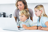 Mother and children using laptop