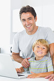 Smiling father and son in kitchen