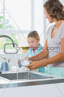 Mother and daughter doing the washing up