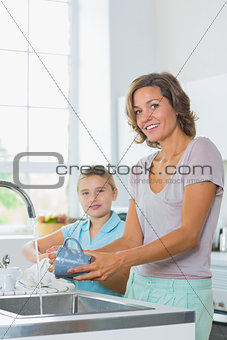 Mother washing up with daughter drying