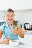 Smiling girl having cereal