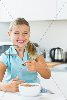 Smiling girl having cereal