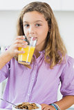 Girl having orange juice at breakfast
