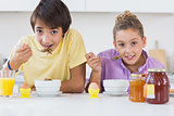 Siblings eating cereal for breakfast