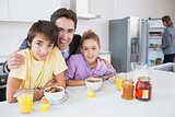 Happy father and children at breakfast