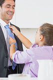 Daughter adjusting fathers tie