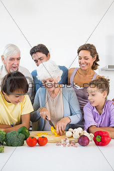 Family watching grandmother slicing pepper