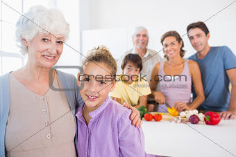 Grandmother and granddaughter standing beside counter