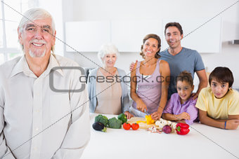 Happy grandfather standing by kitchen counter